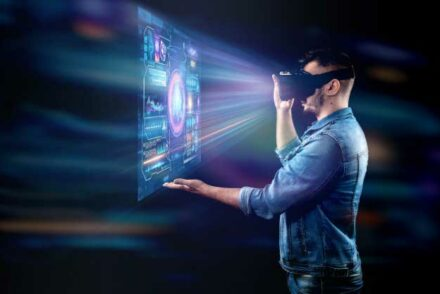 A man using a Virtual Reality headset which lids up a holographic display in front of him